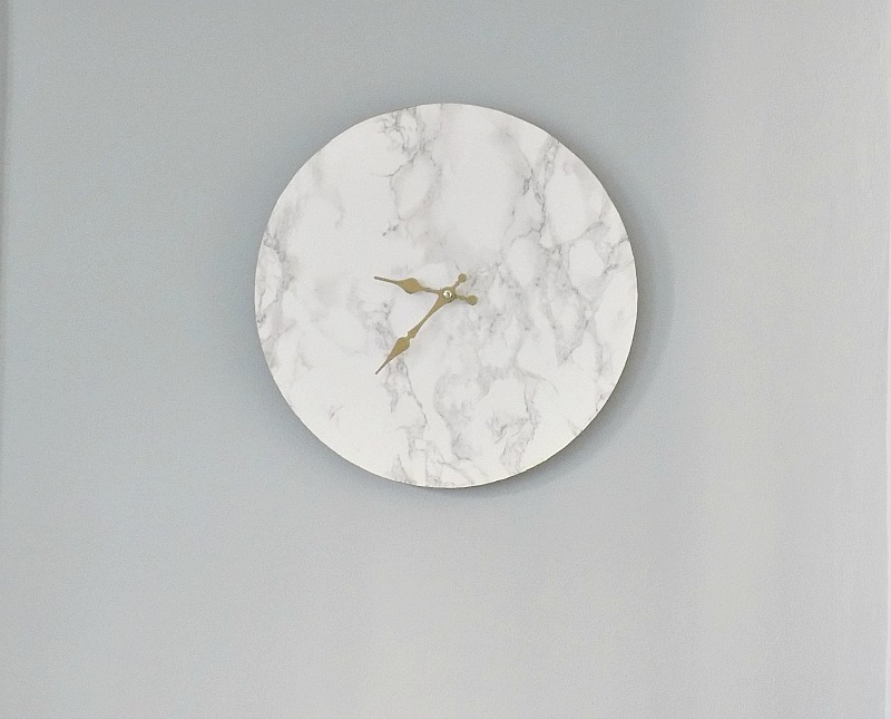 Faux marble clock on gray wall