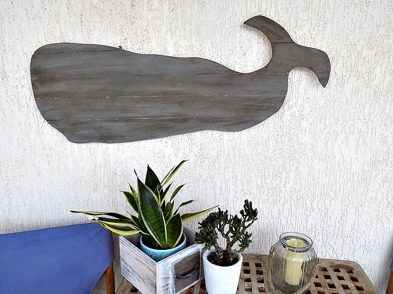 Μια ξύλινη διακοσμητική φάλαινα στον τοίχο του καλοκαιρινού μπαλκονιού μας