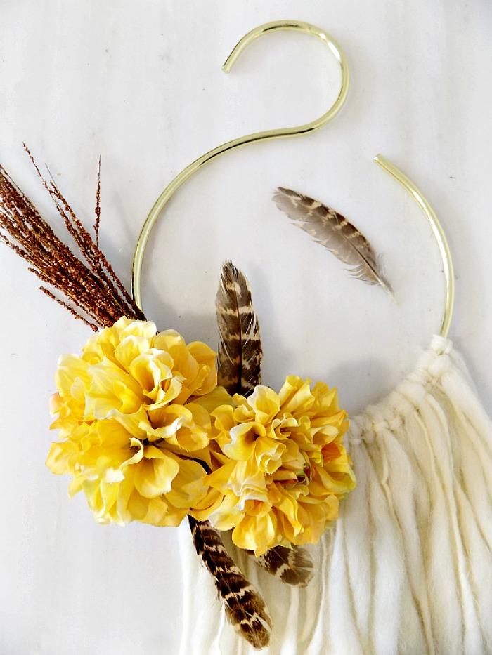 Ψεύτικα λουλούδια και φτερά πάνω σε boho glam φθινοπωρινό στεφάνι