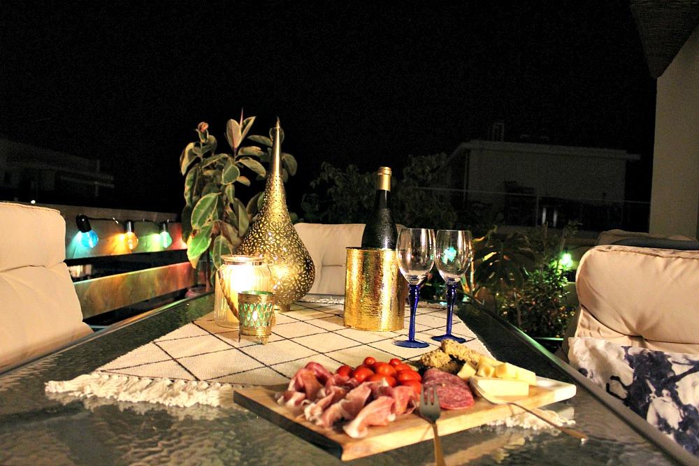 Καλοκαιρινή νύχτα στην βεράντα, ποικιλία τυριών και αλλαντικών και παγωμένο κρασί