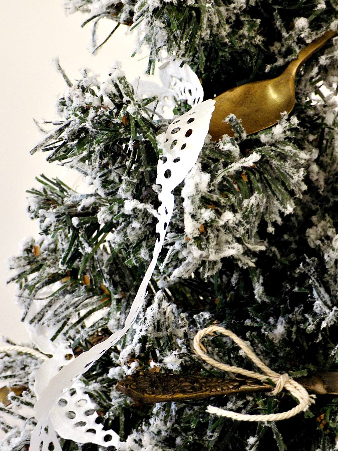 Vintage silver cuttlery on christmas tree, doily paper garland