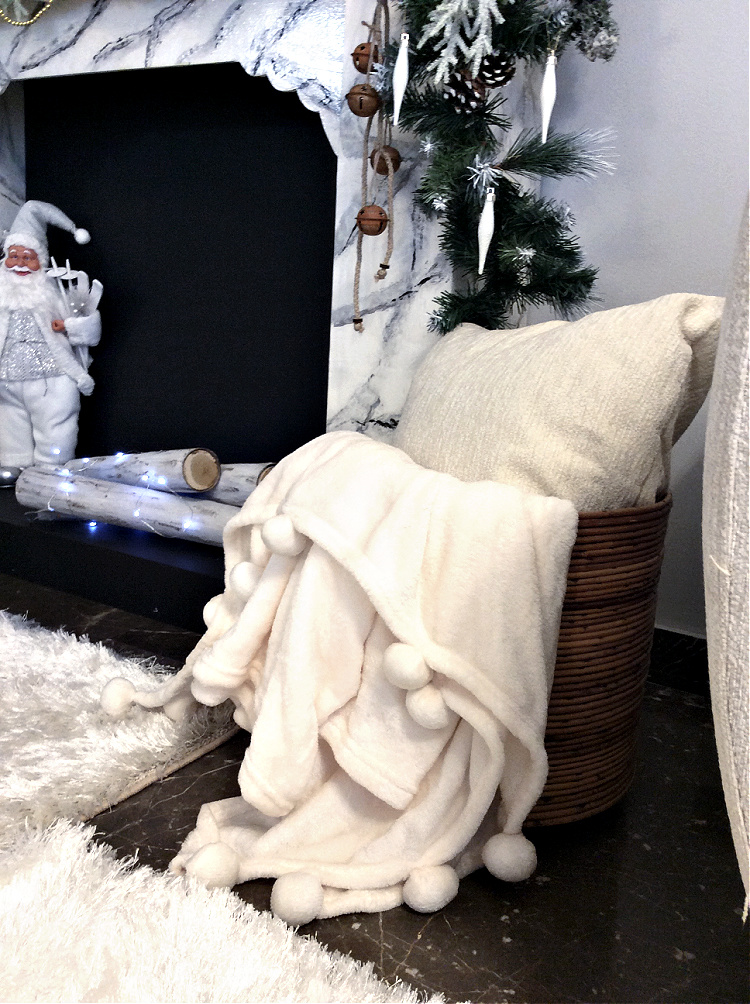 Λευκό μαξιλάρι και ριχτάρι δίπλα στο τζάκι