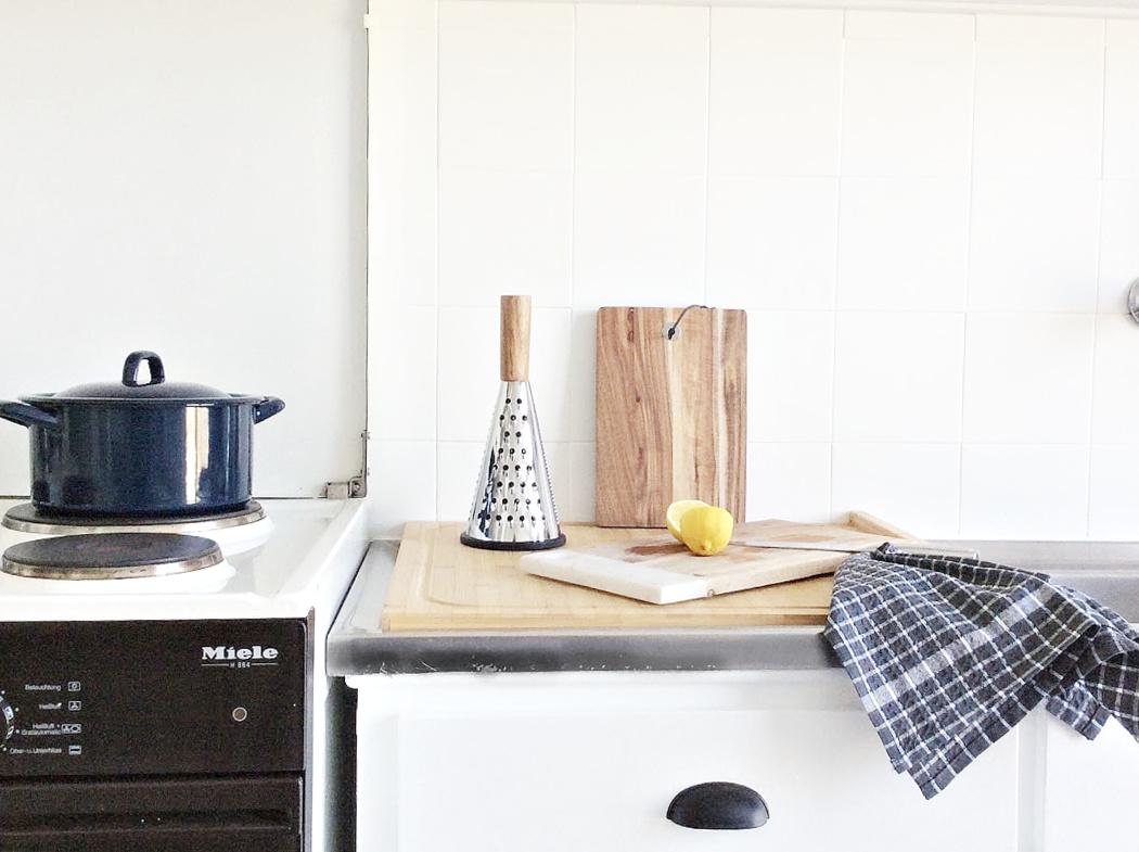 Κουζίνα λευκά ντουλάπια και πλακάκια με ξύλινες λεπτομέρειες